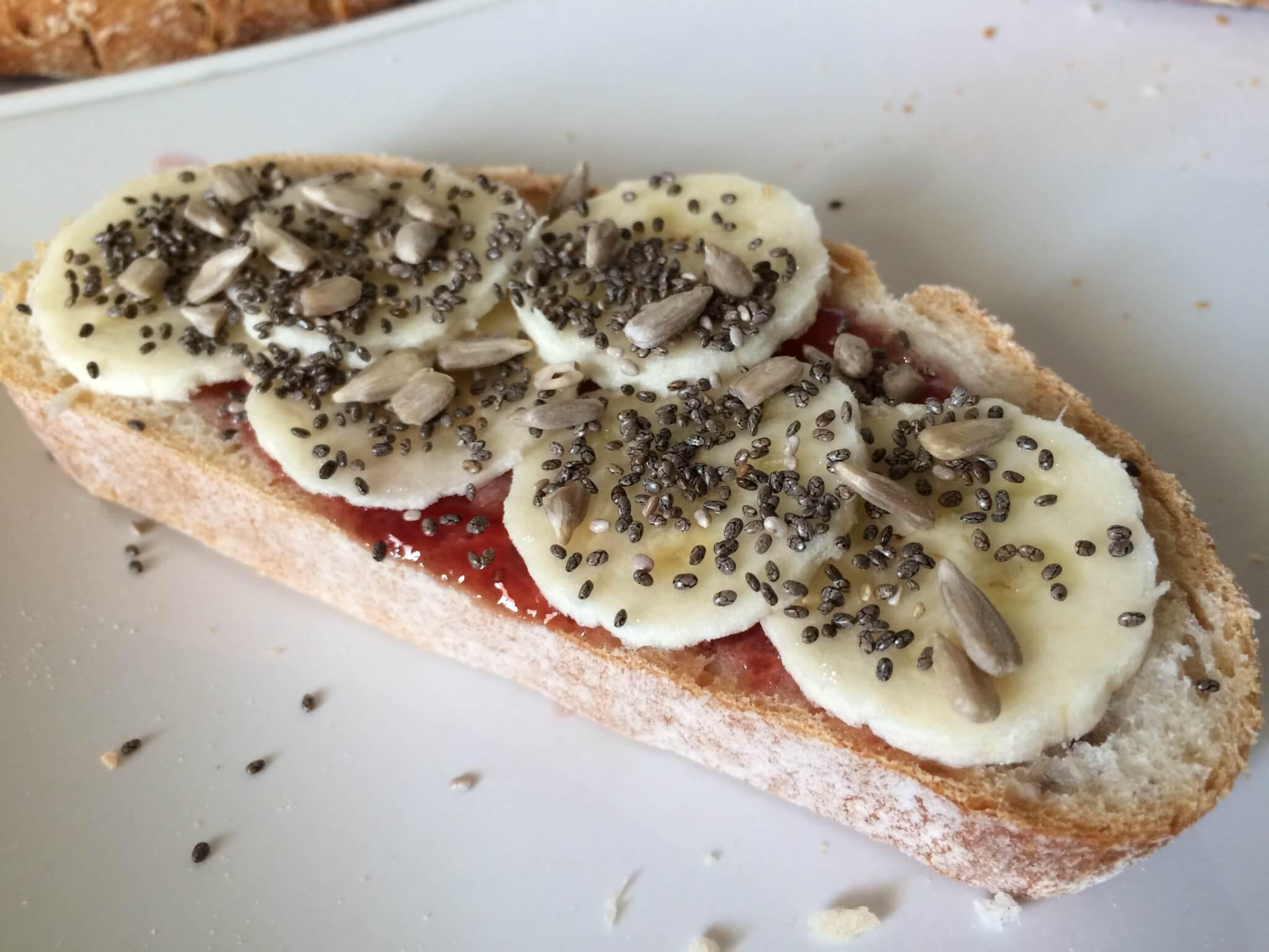 Pão com banana, doce de morango e sementes de chia e girassol